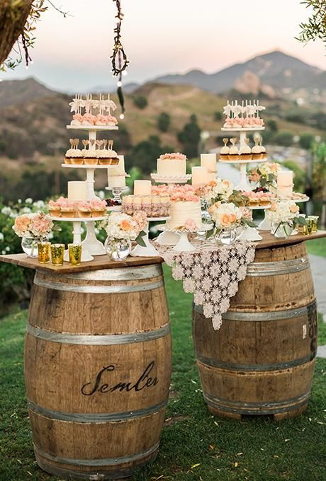 A pink-and-cream dessert bar on wooden barrels featuring miniature cakes and cupcakes